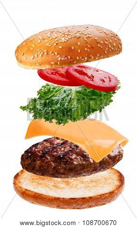 delicious burger with flying falling ingredients on white background