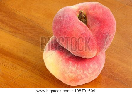 Closeup of Saturn Peaches, known as flat Donut peach on a wooden background