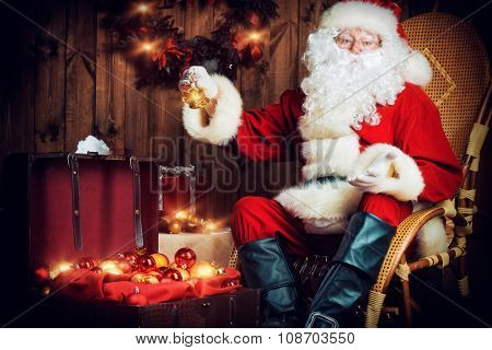 Good old Santa Claus with Christmas gifts at his wooden house.