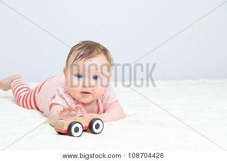 cute little girl reaching car toy