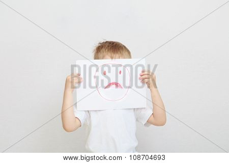 little boy holding sad face mask