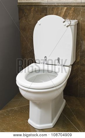 White toilet in brown bathroom with tile floor.