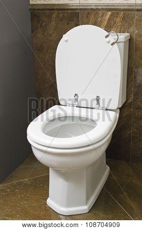 White toilet in brown bathroom with tile floor.