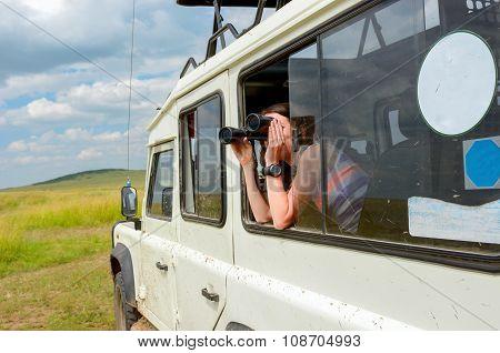 Woman tourist on safari in Africa, travel in Kenya, watching wildlife in savanna with binoculars