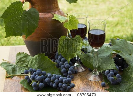 Red wine in stemware standing on the wooden background with grapes and green leaves