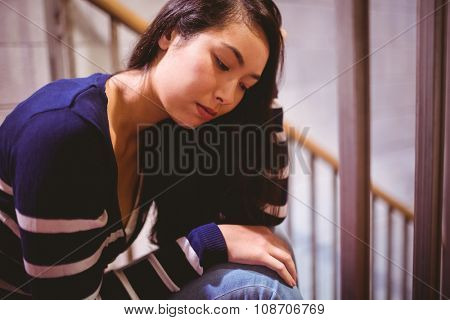 Worried student sitting in hallway at the university