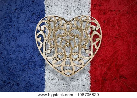 Bronze heart on France flag in background
