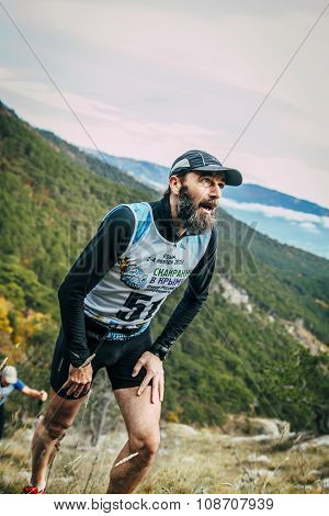 male athlete middle-aged rises to top of mountain