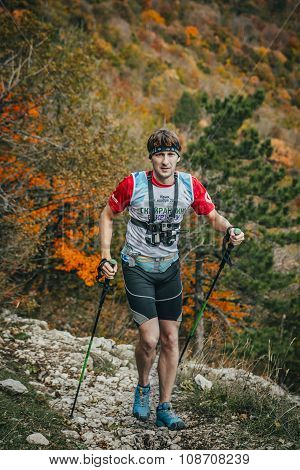 young male athlete is on a mountain trail with walking sticks