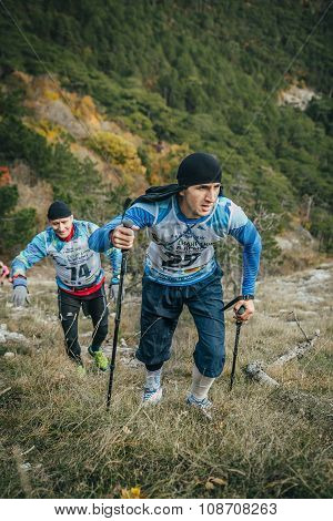 young athlete marathon runner is ahead of his opponent on a mountain trail