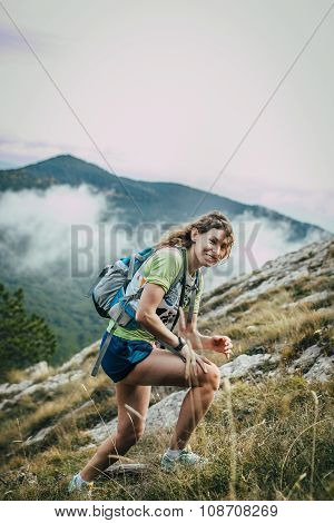 beautiful smiling girl on mountainside. in background clouds