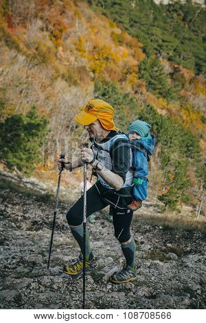male athlete goes to mountain behind him a small child