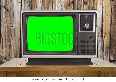 Old television with chroma key green screen and rustic wood wall.