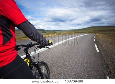 Biker rides on road at sunny summer day in Iceland