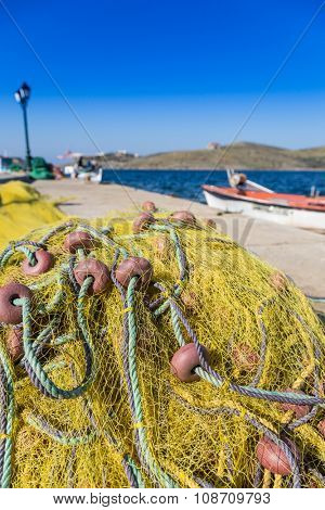 Photo of yellow tangled fishing net lying on pier against of beautiful seascape in summer
