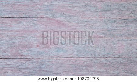 Close-up of pale grey wooden horizontal planks with red and blue tints