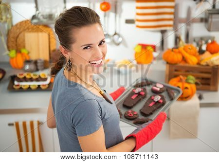 Housewife Removing From Oven Tray With Halloween Biscuits