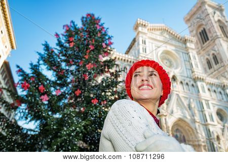 Happy Young Woman Standing Near Christmas Tree In Florence