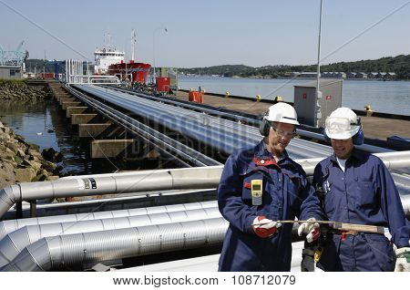 refinery pipelines leading to ships with two oil and gas workers