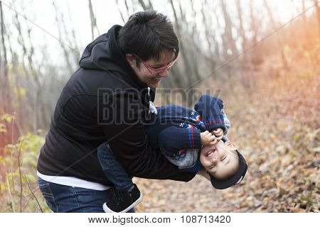 family planting tree with  spade outdoor in autumn