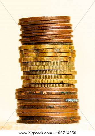 Old antique coins copper and brass metal stacked on one another on a blurred background