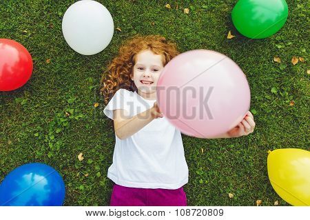 Happy Little Girl Holding Colored Balloon, Lies On Green Grass At Summer Park. Happy Childhood, Birt
