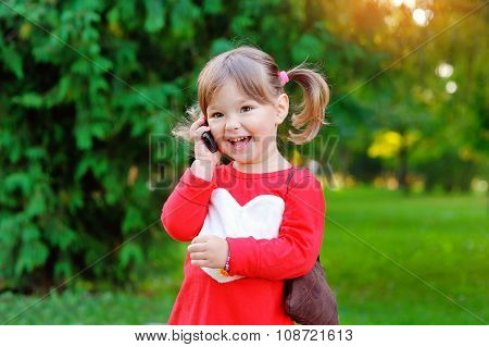 Child Speaks On The Phone In The Park