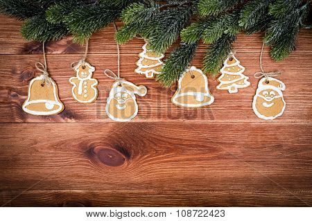 Christmas cookies with coniferous branch on the wooden background.