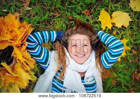 Laughing Girl Lying On The Grass In The Autumn