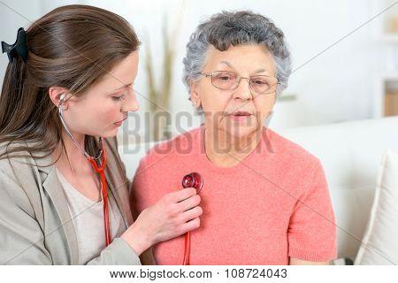 Checking senior woman's heartbeat
