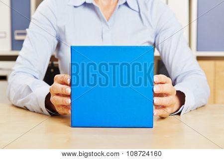 Hands of business man holding blue gift on office desk
