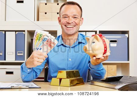 Happy business man with Euro money and gold bars and piggy bank