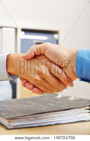 Business people shake hands in office after contract deal