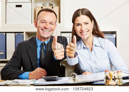 Two happy business people in office holding their thumbs up