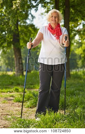 Elderly smiling woman doing nordic walking in a forest in summer