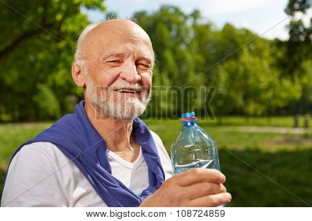 Thirsty senior man drinking a bottle of water in summer