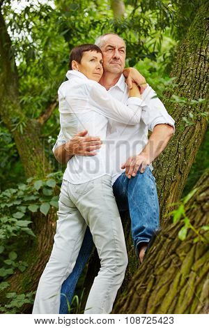 Pensive senior couple leaning on tree in forest in summer