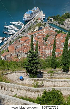 tourist with a open blue umbrella up the stairs from the Old Kotor lead to the St. John fortification, Montenegro