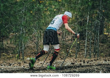 athlete running with nordic walking poles in compression socks