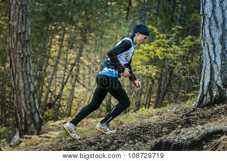 male athlete climbs a steep hill in woods