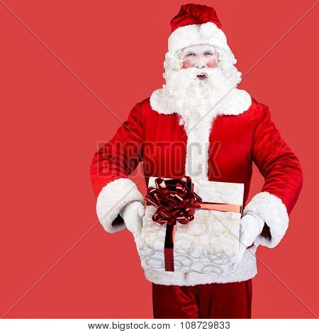 Santa Claus with gift posing on red background