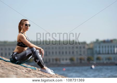 beautiful wonan listening to music and relaxing after a workout on the waterfront