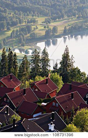 Scandinavian village with scenic lake and misty landscape