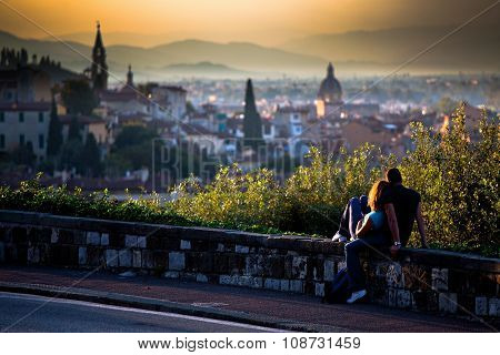 A couple in love watching a scenic sunset over a panorama of Florence