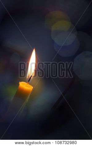 Candle burning in soft bokeh background