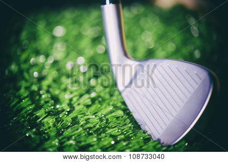 Golf club head open face iron detail against turf