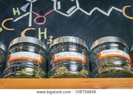 Medical marijuana jars against board with THC formula