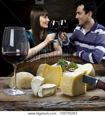 couple taking red wine and eating cheese in the restaurant