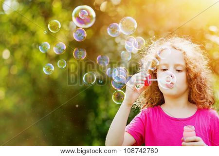 A Little Girl Blowing Soap Bubbles In Summer Park. Background Toning For Instagram Filter.