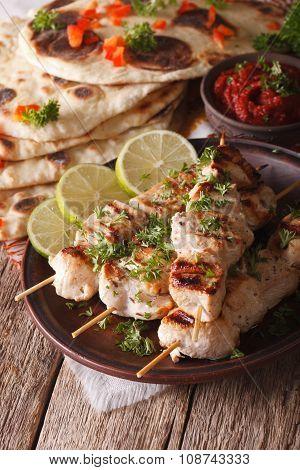 Kebabs Chicken Tikka On Skewers Close-up And Flat Bread. Vertical